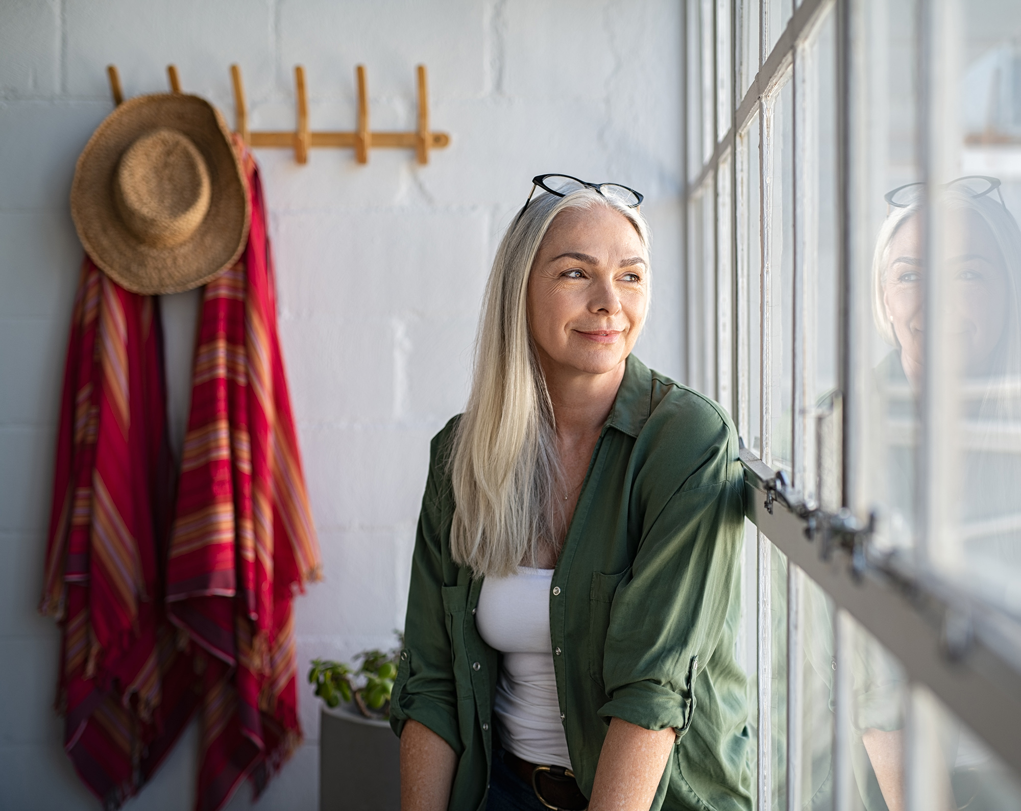 Smiling mature woman looking outside window with a pained expression. Find relief with divorce counseling near katy, tx. Divorce recovery in katy, tx can help you live again. If you need help healing from divorce in katy, tx call now!
