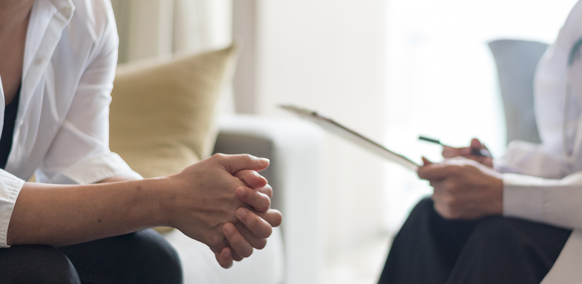 woman holding her hands together while talking to a relationship therapist