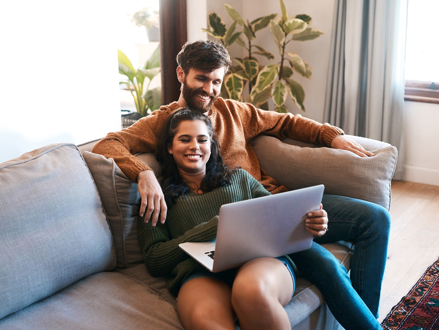 Shot of a young couple using a laptop while relaxing on the sofa at home