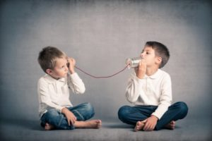 2 boys happily playing with tin can telephones during family therapy in Katy, TX 77494