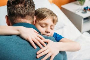 A father hugging his son and showing compassion after their family session in Katy TX 77494