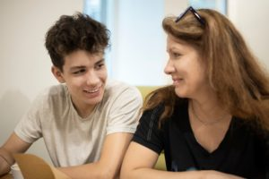 Son and mother sitting on couch smiling at each other after a family therapy session in Katy. Represents the need for teen therapy and family therapy in katy, tx. Also represents the need for therapy for teens in Katy, tx 77494