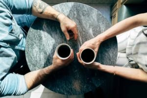 A couple enjoying a cup of coffee talking with one another. One partner experiences anxiety and the other partner is learning to understand his partner's anxiety and how to cope after attending couples counseling in Katy, TX 77494