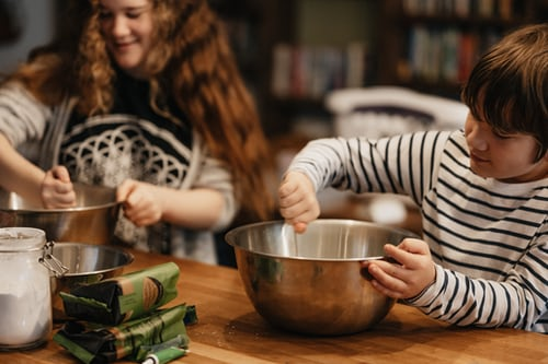 Two kids cooking in the kitchen. Represents the need for family counseling to help parenting children with ADHD in Katy, TX 77494