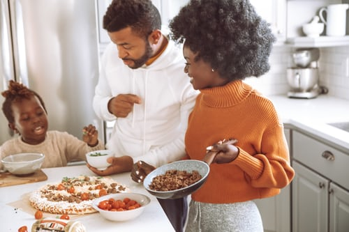 An African American family in the kitchen spending quality time together. Represents the need for family therapy to learning parenting tips in Katy, TX 77494